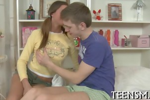 Teen unbuttons her lover's jeans